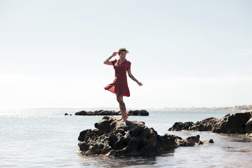 Spain, Mallorca, tattooed young woman standing on a rock looking at distance - LOTF00021