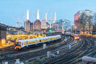 United Kingdom, England, London, view of railtracks and trains in the evening, former Battersea Power Station and cranes in the background - WPEF01263