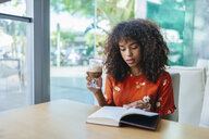 Portrait of young woman drinking  coffee in a cafe while reading a book - KIJF02136