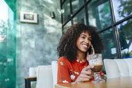 Portrait of happy young woman n the phone a in coffee shop - KIJF02139