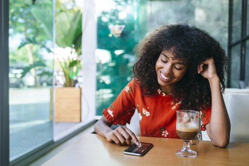 Portrait of smiling young woman  in coffee shop using cell phone - KIJF02142