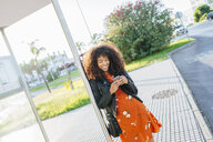 Laughing young woman standing at bus stop looking at cell phone - KIJF02154