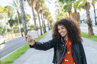 Portrait of smiling young woman taking selfie with smartphone - KIJF02160