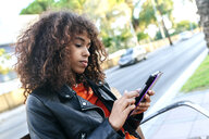 Young woman sitting on a bench using digital tablet - KIJF02163