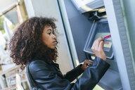 Woman using credit card at ATM - KIJF02166