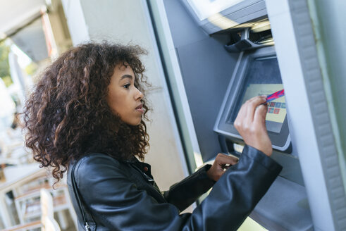 Woman using credit card at ATM - KIJF02166
