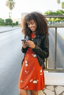 Portrait of smiling young woman standing at roadside looking at smartphone - KIJF02169