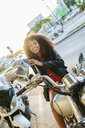 Portrait of laughing young woman wsitting on motorcycle putting on helmet - KIJF02172