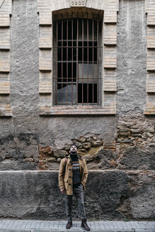 Spain, Igualada, man standing at rundown industrial building in the town - JRFF02283