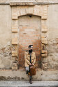 Spain, Igualada,man with backpack standing at rundown building - JRFF02292