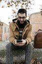 Spain, Igualada, smiling man sitting down using cell phone in the autumnal town - JRFF02301