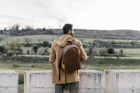 Spain, Igualada, rear view of man with backpack standing at concrete wall - JRFF02313