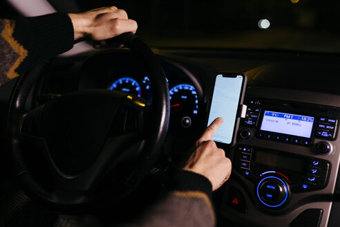 Man using cell phone with road maps in the car at night - JRFF02322