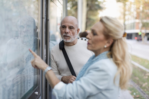 Spain, Barcelona, senior couple checking the timetable at tram stop in the city - MAUF02235