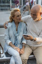 Spain, Barcelona, senior couple sitting at tram stop in the city sharing smartphone with earbuds - MAUF02241