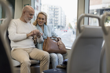Senior couple sitting in a tram checking the time - MAUF02247
