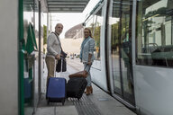 Spain, Barcelona, senior couple with baggage at tram stop in the city - MAUF02250