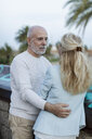 Spain, Barcelona, senior couple embracing at the promenade - MAUF02253