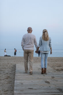 Spain, Barcelona, rear view of senior couple walking hand in hand on the beach at dusk - MAUF02256