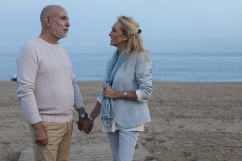 Spain, Barcelona, happy senior couple hand in hand on the beach at dusk - MAUF02259