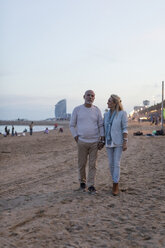 Spain, Barcelona, senior couple walking hand in hand on the beach at dusk - MAUF02262