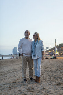 Spain, Barcelona, happy senior couple on the beach at dusk - MAUF02265