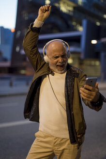 Spain, Barcelona, excited senior man with headphones and cell phone in the city at dusk - MAUF02271