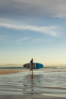 Spain, Andalusia, Tarifa, man walking with stand up paddle board on the beach - KBF00359
