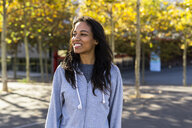 Portrait of a smiling woman, standing in a park - GIOF05300