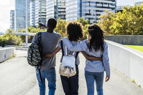 Three friends exploring the city, walking down the street, arm in arm - GIOF05321