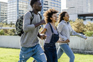 Three friends running on a lawn in the city, laughing - GIOF05324