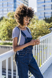Young woman standing on a bridge, using smartphone - GIOF05333