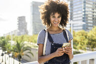 Young woman standing on a bridge, holding smartphone - GIOF05336
