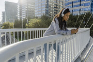 Young woman standing on a bridge, listening music, using smartphone - GIOF05360