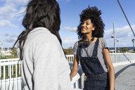Girl friends meeting on a bridge, having fun - GIOF05363