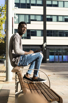 Young man sitting on a bench in the city, using laptop - GIOF05384