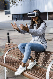 Young woman sitting on a bench, using VR goggles, reaching out with her hands - GIOF05390
