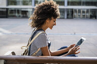 Mid adult woman with curly hair, sitting on a bench, using digital tablet - GIOF05396