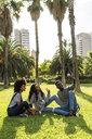 Friends sitting on grass, having fun, using smartphone - GIOF05405