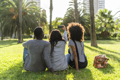 Three friends sitting in a park, watching the sunset, taking a selfie - GIOF05432