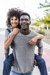 Young man carrying his girlfriend piggyback in the street - GIOF05438