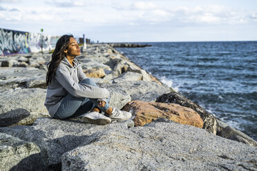 Young woman relaxing on the beach, sitting on rocks, with eyes closed - GIOF05447