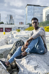 Young man sitting on rocks at the beach, relaxing - GIOF05450