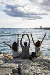 Three friends sitting on the beach, lookin at the sea, cheering, rear view - GIOF05453