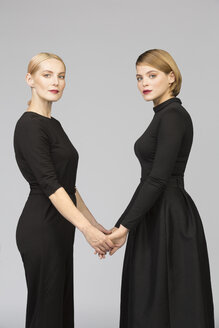 Studio portrait of mother and adult daughter holding hands - VGF00152