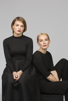Studio portrait of mother and adult daughter sitting down - VGF00161