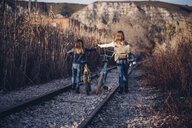 Two girls walking on the train track with bicycles - OCMF00187