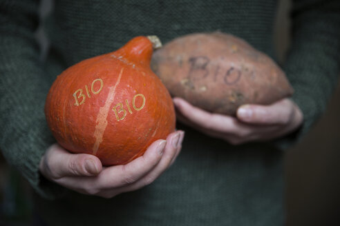 Woman's hands holding organic Hokkaido pumpkin and sweet potatoe with Smart Branding - MAMF00293