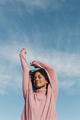 Portrait of smiling young woman wearing pink pullover against sky - LOTF00032