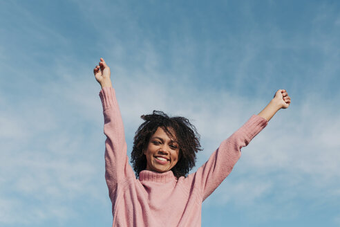 Portrait of smiling young woman against sky raising hands - LOTF00035